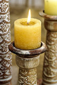 Golden candle on oriental candle holder — Stock Photo