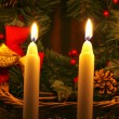 Golden candles in front of christmas wreath.Selective focus. — Stock Photo