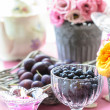 Goblet of blackberries, basket of plums and bouquet of eustoma — Stock Photo #26514289