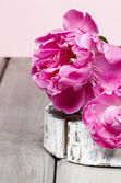 Pink peony flower on wooden table — Stock Photo