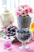 Goblet of blackberries, basket of plums and bouquet of eustoma — Stock Photo