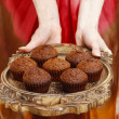 Woman holding a wooden tray with chocolate muffins — ストック写真