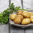 Basket of potatoes on grey wooden table — Stock Photo
