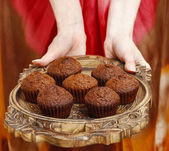 Woman holding a wooden tray with chocolate muffins — Stock Photo