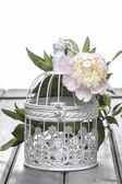 Pink peony in wicker basket on rustic wooden table. — Stock Photo