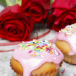 Muffins covered with pink icing and colorful sprinkles on wooden — Stock Photo #26747875