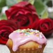 Muffins covered with pink icing and colorful sprinkles on wooden — Stock Photo #26747929
