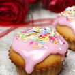 Muffins covered with pink icing and colorful sprinkles on wooden — Stock Photo #26748001