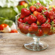 Glass bowl of fresh ripe strawberries on rustic wooden table in — Stock Photo