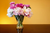 Bouquet of peonies in glass vase on wooden table — Stock Photo
