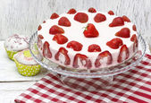Strawberry cake on red and white table cloth — Stock Photo