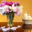 Bouquet of peonies in glass vase and basket of candles — Stock Photo