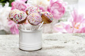 Pastel cake pops on rustic wooden table. Stunning peony flowers — Stock Photo