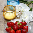 Strawberries, candles and white peony flower on wooden table — Stock Photo