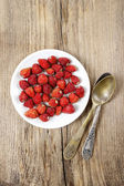 Wild strawberries on white plate, on wooden table. Copy space — Stock Photo