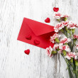 Pink carnations, hearts and red envelope isolated on wooden back — Stock Photo