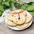 Round biscuits with red bow in spring setting. Wooden table — Stock Photo