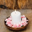 White candle among carnation flowers in vintage wooden bowl — Stock Photo