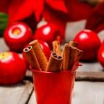 Bucket of cinnamon sticks on wooden table. Christmas setting — Stock Photo #27595941