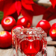 Glass candle holder with heart shape on wooden table, apples — Stock Photo #27596093