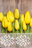 Yellow tulips on wooden background — Stock Photo