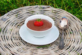 Pudim de chocolate cremoso em bandeja de vime cinza no jardim — Fotografia Stock