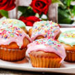 Muffins covered with pink icing and colorful sprinkles on wooden — Stock Photo