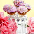 Cake pops on wooden background among carnation flowers — Stock Photo