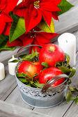 Rustik ahşap mum arasında kırmızı olgun elma gümüş kova — Stok fotoğraf