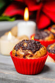 Poppy-seed muffins in christmas table setting. White candle — Stock Photo