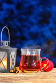 Iron lantern, steaming cup of tea and red apples on wooden table — Stock Photo