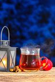 Latarnia żelaza, parze filiżankę herbaty i czerwonego jabłka na drewnianym stole — Zdjęcie stockowe