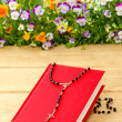 New red Holy Bible and black rosary on old wooden surface — Stock Photo