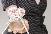 Young woman holding bouquet of carnation flowers — Stock Photo