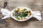 Fish in baking paper on rustic rough wooden table. Copy space. — Stock Photo