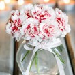 Bouquet of carnation flowers in glass vase on wooden table — Stock Photo #28169965