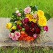 Fabulous bouquet of colorful roses on wooden tray in fresh sprin — Stock Photo #28173135