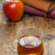Glass of hot steaming tea on wooden table. Pile of books — Stock Photo