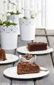 Chocolate cake on grey wooden table. Bookshelves in the back — Stock Photo