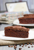 Chocolate cake on white plate, on hessian. Coffee beans — Stock Photo