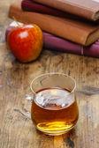 Vaso de té humeante sobre mesa de madera. pila de libros — Foto de Stock
