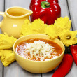 Bowl of tomato soup, fresh flowers and vegetables in the backgro — Stock Photo #28362379