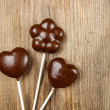 Chocolate cake pops in heart and flower shapes on wood — Stock Photo #28365167