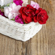 Stock Photo: Red, pink and white carnation flowers in wicker basket on wooden