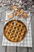 Homemade pie on checkered napkin, on wooden table. Fresh eggs — Stock Photo