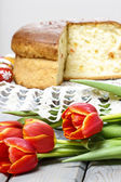 Red tulips in front of easter yeast cake. Selective focus — Stock Photo