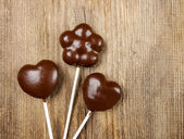 Chocolate cake pops in heart and flower shapes on wood — Stock Photo
