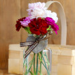 Bouquet of pink, red and white carnation flowers in glass vase. — Photo