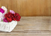 Red, pink and white carnation flowers in wicker basket — Stock Photo