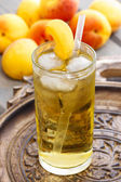 Peach drink. Apricot pie on cake stand in the background — Stock Photo